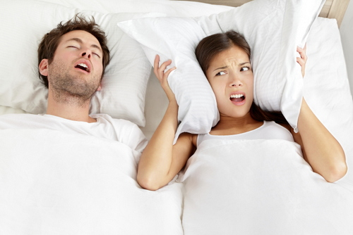 Man snoring in bed next a woman who is upset and has a pillow covering her ears.